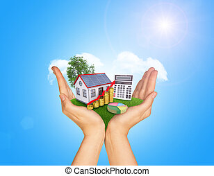 Hands holding green grass with house on ground. Standing...