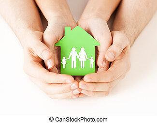 hands holding green house with family - real estate and ...