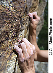 hands holding grip - hands of a man climbing on granite