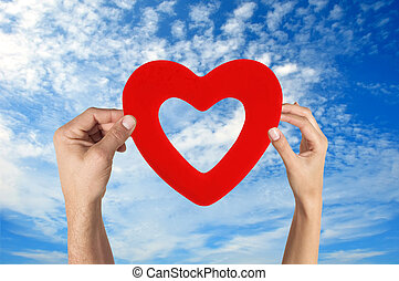 hands holding heart shape with blue sky background