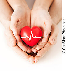 hands holding heart with ecg line - health, medicine and...