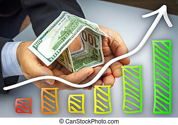 Hands holding house of money - real estate