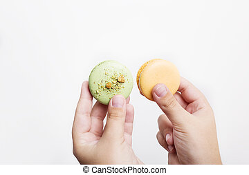 Hands holding macarons isolated on white background