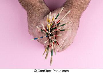 hands holding mikado sticks