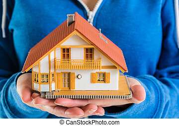 Hands holding miniature house model