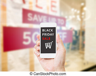 Hands holding mobile phone with Black Friday sale on screen on blurred image of shopping mall
