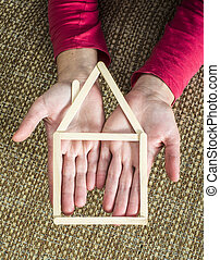 Hands holding model house made of wooden sticks