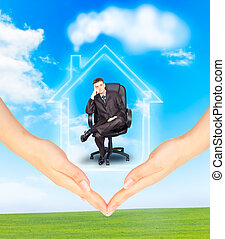 Hands holding model of a house with businessman