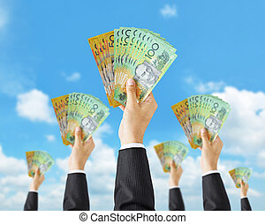 Hands holding money - Australian dollar (AUD) banknotes