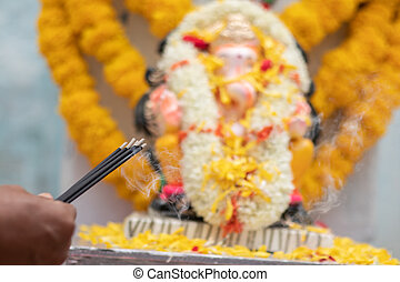 Hands Holding or offering incense or agarbatti stick in front of lord vinayaka or Ganesha while praying or worshiping during festival ceremony.