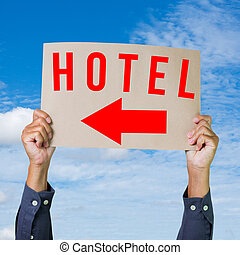 Hands holding paper with hotel direction sign