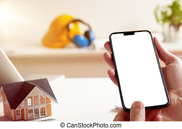 Hands holding phone while planning a future house
