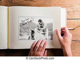 Hands holding photo album with picture of senior couple. Studio