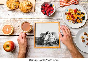 Hands holding picture of seniors, breakfest meal. Studio shot.