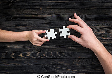 hands holding pieces of white puzzle