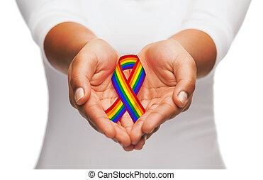 hands holding rainbow gay pride awareness ribbon