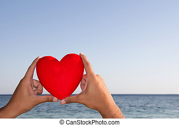 Hands holding red heart with blue sky and sea horizon in the background.