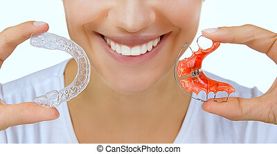 Beautiful smiling girl holding retainer for teeth (dental braces) and individual tooth tray