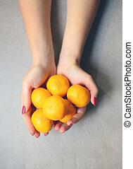 Hands holding ripe of fresh mandarines - Top view