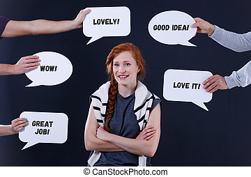Hands holding speech bubbles around a woman