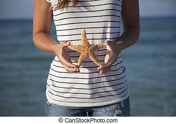 Hands holding starfish