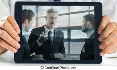 Hands holding tablet showing business meeting video