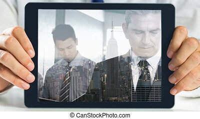 Hands holding tablet showing businessman video