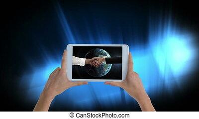Hands holding tablet showing handshake video