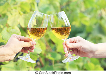 Hands holding the glasses with wine