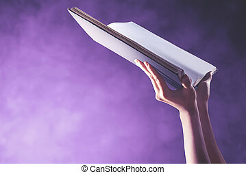 Hands holding the Quran with a colored background