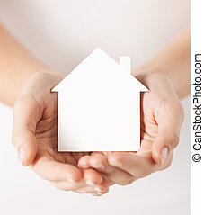 hands holding white paper house