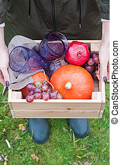 Hands holding wooden box with pumpkin, grape, pomegranate and glasses of wine. Close up.