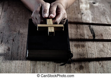Hands holding wooden cross over holy bible on wooden table background. christian concept.