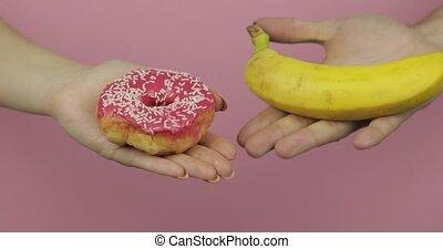Hands holds donut and banana. Choice donut against banana....