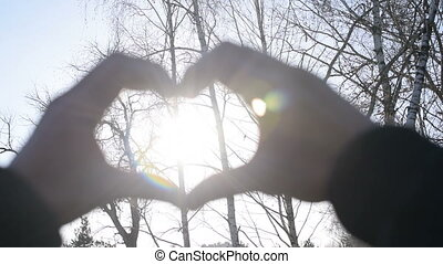 Hands in form of a heart with sunshine