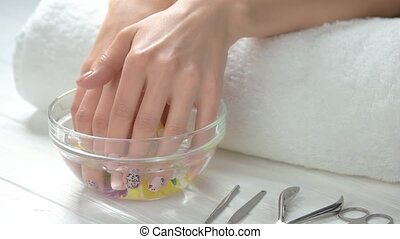 Hands in glass bow with chrysanthemums. Young woman in spa...