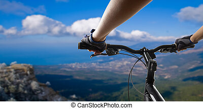 Hands in gloves holding handlebar of a bicycle. Mountain Bike cyclist riding single track. Healthy lifestyle active athlete doing sport.