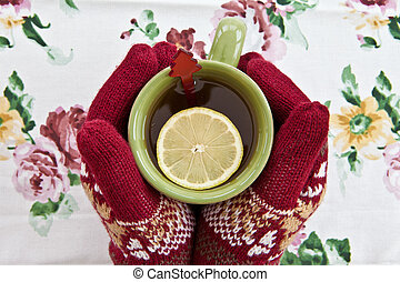 Hands in knitted gloves holding a mug