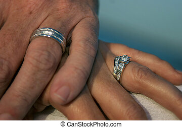 Married couple holding hands, showing wedding rings