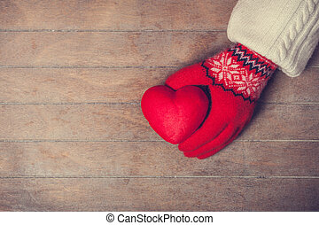 Hands in mittens holdin heart toy