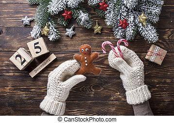 Hands in mittens holding gingerbread men