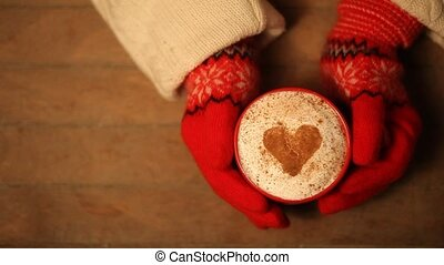 Hands in mittens holding hot cup of coffee