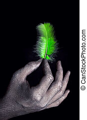 hands in silver paint holding light green feather