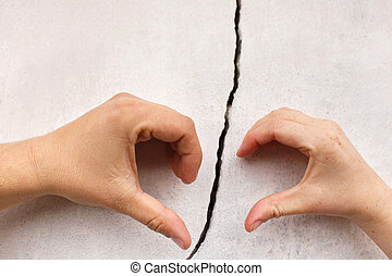 hands in the shape of heart on cracked wall