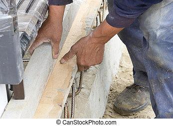 Hands installing formworks