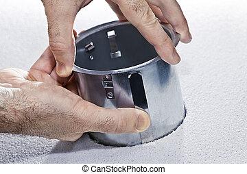 Hands installing metal pot light fixture - Hands installing...