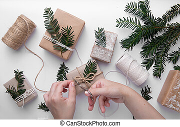 Hands is making gifts for Christmas on white background - ...