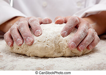 hands kneading bread dough on a cutting board