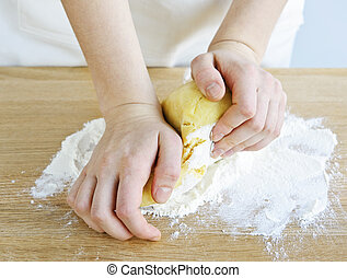 Hands kneading ball of dough with flour on cutting board