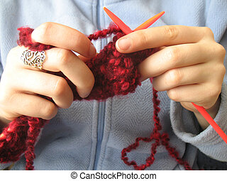 Detail of ands knitting magenta scarf against a blue background